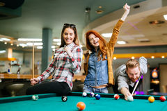 Happy friends enjoying playing pool Royalty Free Stock Image
