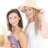 Happy friends enjoying the summer. Happy female friends enjoying the summer in their casual sleeveless dresses and straw sunhats Royalty Free Stock Photography