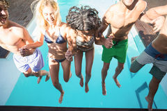 Happy friends enjoying at the swimming pool. Happy friends holding hands jumping in the swimming pool Stock Photography