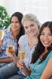Happy friends enjoying white wine together looking at camera. At home on the couch Stock Photos