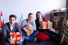 Young woman and two man posing and smiling with holiday boxes wi royalty free stock images