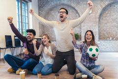 Happy friends or football fans watching soccer on tv. And celebrating victory. Friendship, sports and entertainment concept Stock Photos