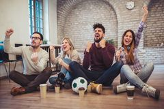 Happy friends or football fans watching soccer on tv and celebrating victory. Friendship, sports and entertainment concept Royalty Free Stock Image
