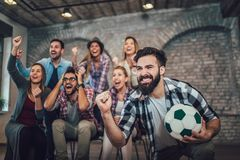 Happy friends or football fans watching soccer on tv and celebrating victory royalty free stock photos