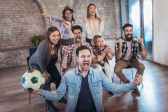 Happy friends or football fans watching soccer on tv and celebrating victory. Friendship, sports and entertainment concept Stock Images