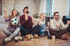 Happy friends or football fans watching soccer on tv and celebrating victory. Friendship, sports and entertainment concept Royalty Free Stock Images