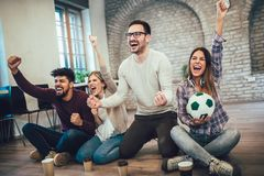 Happy friends or football fans watching soccer on tv and celebrating victory. Friendship, sports and entertainment concept Stock Photos