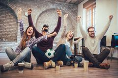 Happy friends or football fans watching soccer on tv and celebrating victory. Friendship, sports and entertainment concept Stock Photo