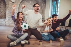 Happy friends or football fans watching soccer on tv and celebrating victory. Friendship, sports and entertainment concept Royalty Free Stock Photography