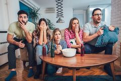 Happy friends or football fans watching soccer on tv and celebrating victory. At home.Friendship, sports and entertainment concept Stock Photo