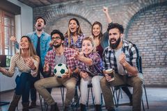 Happy friends or football fans watching soccer on tv and celebrating victory. Friendship, sports and entertainment concept Stock Image