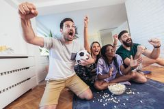 Happy friends or football fans watching soccer on tv and celebrating victory. At home.Friendship, sports and entertainment concept royalty free stock photography