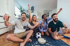 Happy friends or football fans watching soccer on tv and celebrating victory. At home.Friendship, sports and entertainment concept stock image
