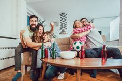 Happy friends or football fans watching soccer on tv. And celebrating victory at home.Friendship, sports and entertainment concept Stock Photography