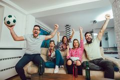 Happy friends or football fans watching soccer on tv Stock Photography