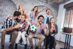 Happy friends or football fans watching soccer on tv. And celebrating victory. Friendship, sports and entertainment concept stock image