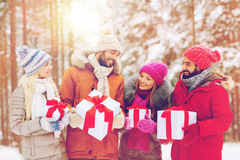 Happy friends with gift boxes in winter forest Stock Photo