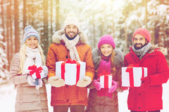 Happy friends with gift boxes in winter forest Stock Photos