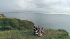 Happy friends and girlfriends having fun and playing musical string instrument while resting on picnic in nature at. Green slope near sea, top view stock footage