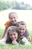 Happy friends girls. Cheerful girls laying on green field royalty free stock image