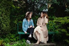 Happy friends girls chatting in spring park, lifestyle portrait.  royalty free stock images