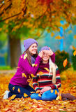 Happy friends, girls playing in vibrant autumn park Royalty Free Stock Photos