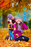Happy friends, girls playing in vibrant autumn park Royalty Free Stock Images