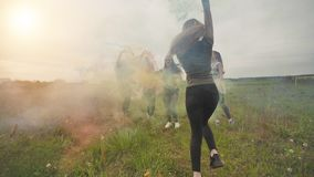 Happy friends girls waving colorful smoke at sunset. Happy friends girls waving colorful smoke at sunset stock video footage