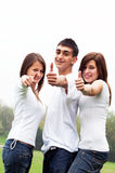 Happy friends giving okey sign. Three young happy friends laughing and giving okey sing Royalty Free Stock Photos
