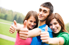 Happy friends giving okey sign. Three young happy friends laughing and giving okey sing Royalty Free Stock Photography