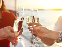 Happy friends with glasses of champagne on yacht. Vacation, travel, sea and friendship concept stock image