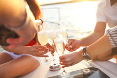 Happy friends with glasses of champagne on yacht. Vacation, travel, sea and friendship concept stock photo