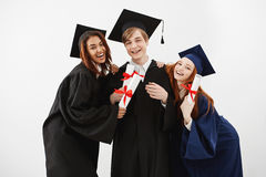 Happy friends graduates smiling holding diplomas looking at camera over white background. Happy beautiful friends graduates smiling holding diplomas looking at Stock Images