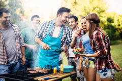 Happy friends enjoying barbecue party. Happy friends grilling meat and enjoying barbecue party outdoors royalty free stock photos