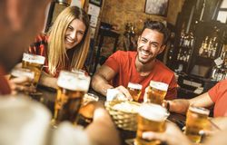 Happy friends group drinking beer at brewery bar restaurant. Friendship concept with young people enjoying time together and having genuine fun at cool royalty free stock image