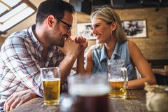 Happy friends having fun at bar - Young trendy couple drinking beer and laughing together. Happy friends group drinking beer at brewery bar restaurant royalty free stock photos