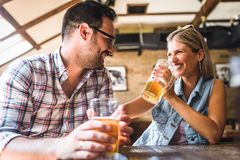 Happy friends having fun at bar - Young trendy couple drinking beer and laughing together. Happy friends group drinking beer at brewery bar restaurant stock photography
