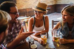 Happy friends having fun at bar - Young trendy people drinking beer and laughing together. Happy friends group drinking beer at brewery bar restaurant royalty free stock image