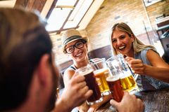 Happy friends having fun at bar - Young trendy people drinking beer and laughing together. Happy friends group drinking beer at brewery bar restaurant royalty free stock images