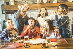 Happy friends group eating pizza at chalet restaurant house. Friendship concept with young people enjoying time together and having genuine fun at italian royalty free stock images