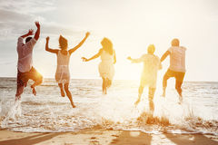 Happy friends group people sunset sea. Happy family or friends at the beach running and jumping in the sunset sea. Friendship or vacations concept Royalty Free Stock Photos