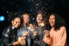 Happy friends. Group of smiling women holding sparklers under confetti Stock Photography