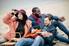 Happy friends with guitar at picnic stock photos