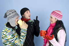 Happy friends have a conversation. Three happy friends  in winter clothes with  sweaters,hats,scarves and gloves holding hot cup of tea  and drinking  ,laughing Royalty Free Stock Photos