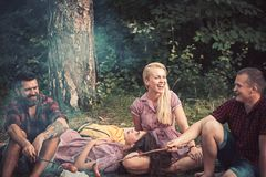 Happy friends have picnic at bonfire in wood. Men and women roast sausages on fire. Boyfriends and girlfriends enjoy. Camping food. People relax on summer royalty free stock photos