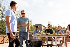 Happy friends having bbq party on rooftop royalty free stock images