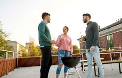 Happy friends having bbq party on rooftop stock image