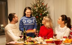 Happy friends having christmas dinner at home royalty free stock photo