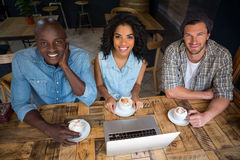 Happy friends having coffee with laptop on wooden table in cafe Royalty Free Stock Photography