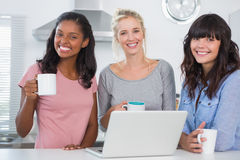 Happy friends having coffee together with laptop Royalty Free Stock Image